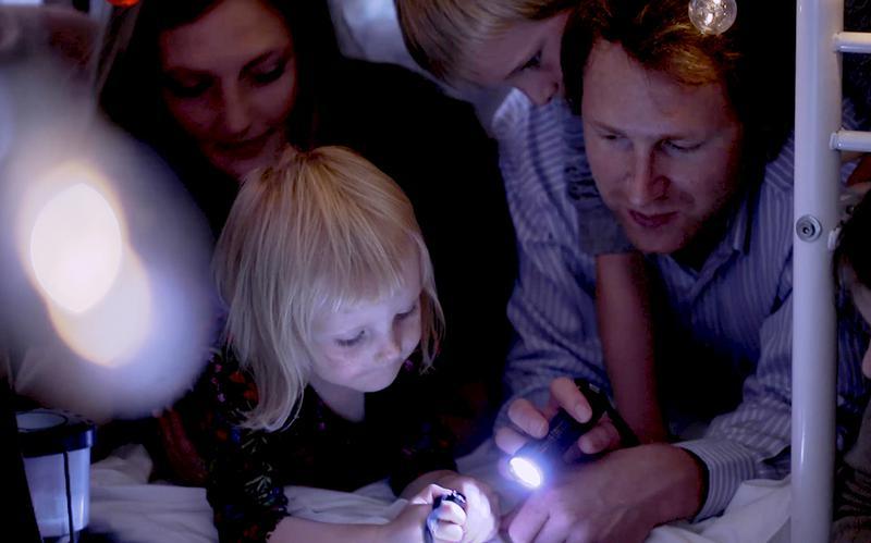 Uma família lê um livro em conjunto, à luz de uma lanterna debaixo do cobertor.
