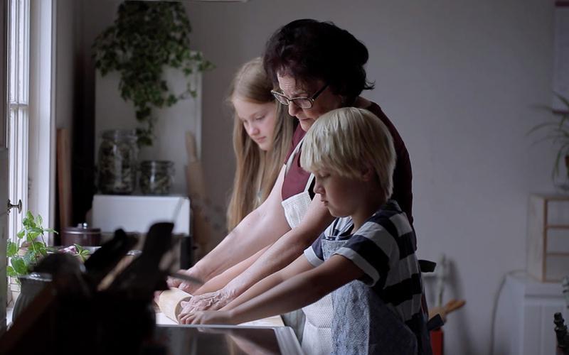 Uma mulher idosa cozinha com os seus netos.