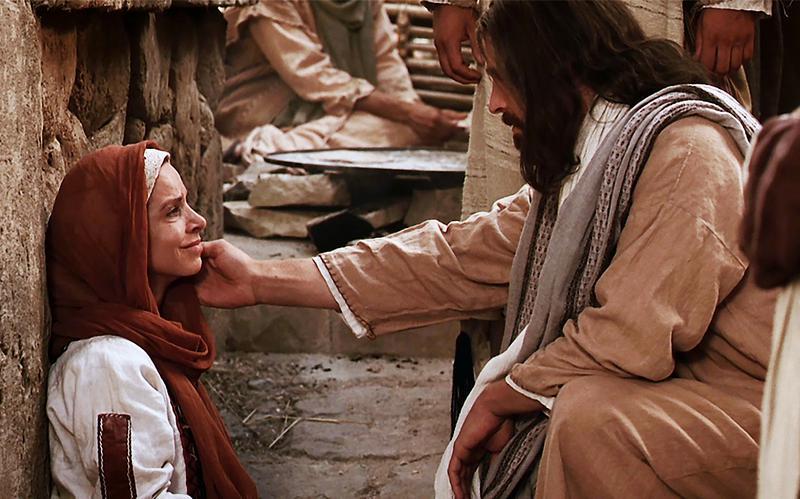 Cristo estende a mão para consolar uma mulher de fé.