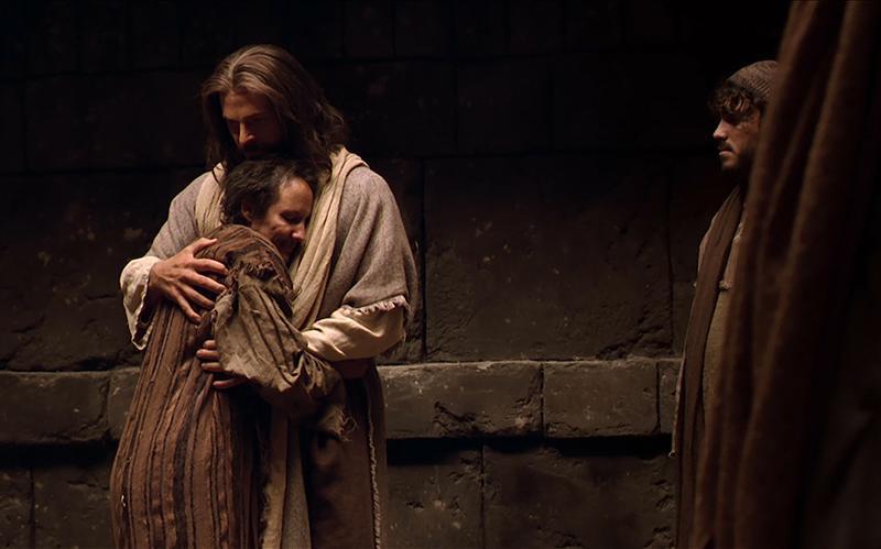 Jesus embraces a man.