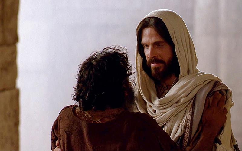 Cristo alza a un hombre que ha caído.