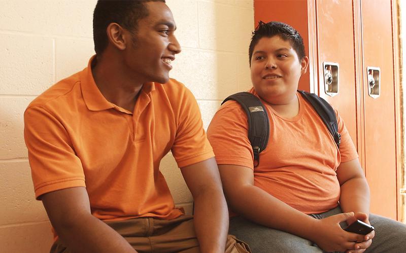 Dwóch przyjaciół rozmawia ze sobą na szkolnym korytarzu.