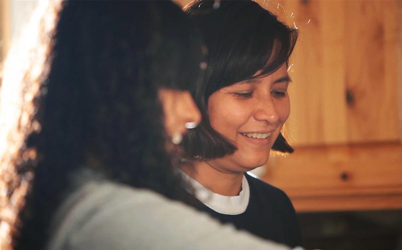 Moeder en dochter glimlachen in de keuken.