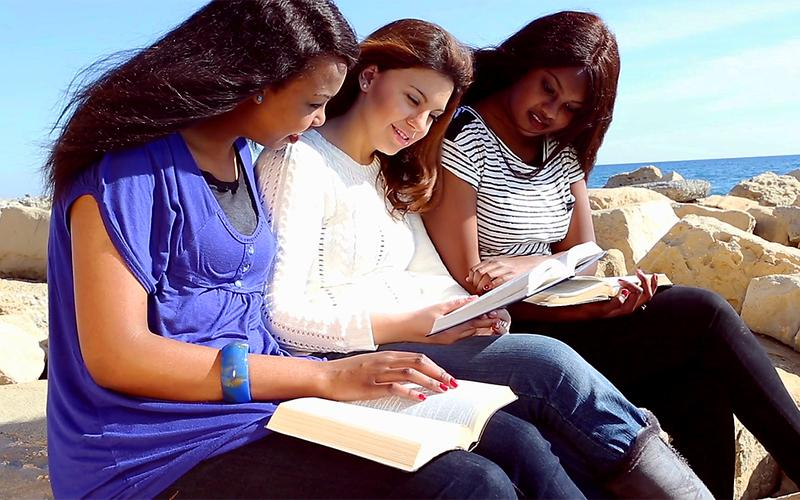 Three girls sit by the sea, reading from the scriptures.