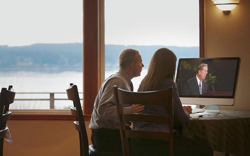a couple is watching on a computer screen an apostle speak