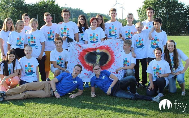 a group of youth with their banner at a FSY conference