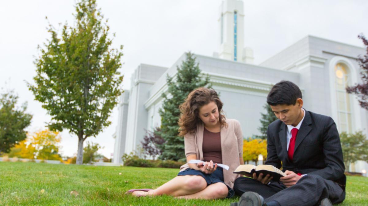 Ein junger Mann und eine junge Frau lesen am Tempelgrundstück die Heiligen Schriften