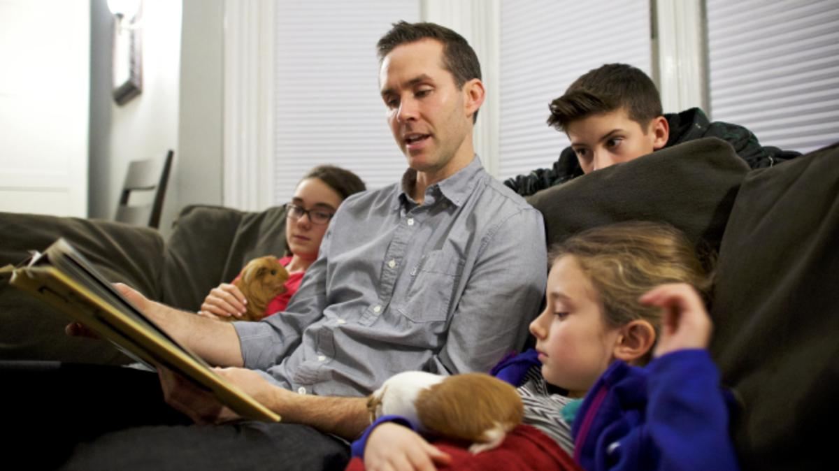Ein Vater liest aus einem Buch vor