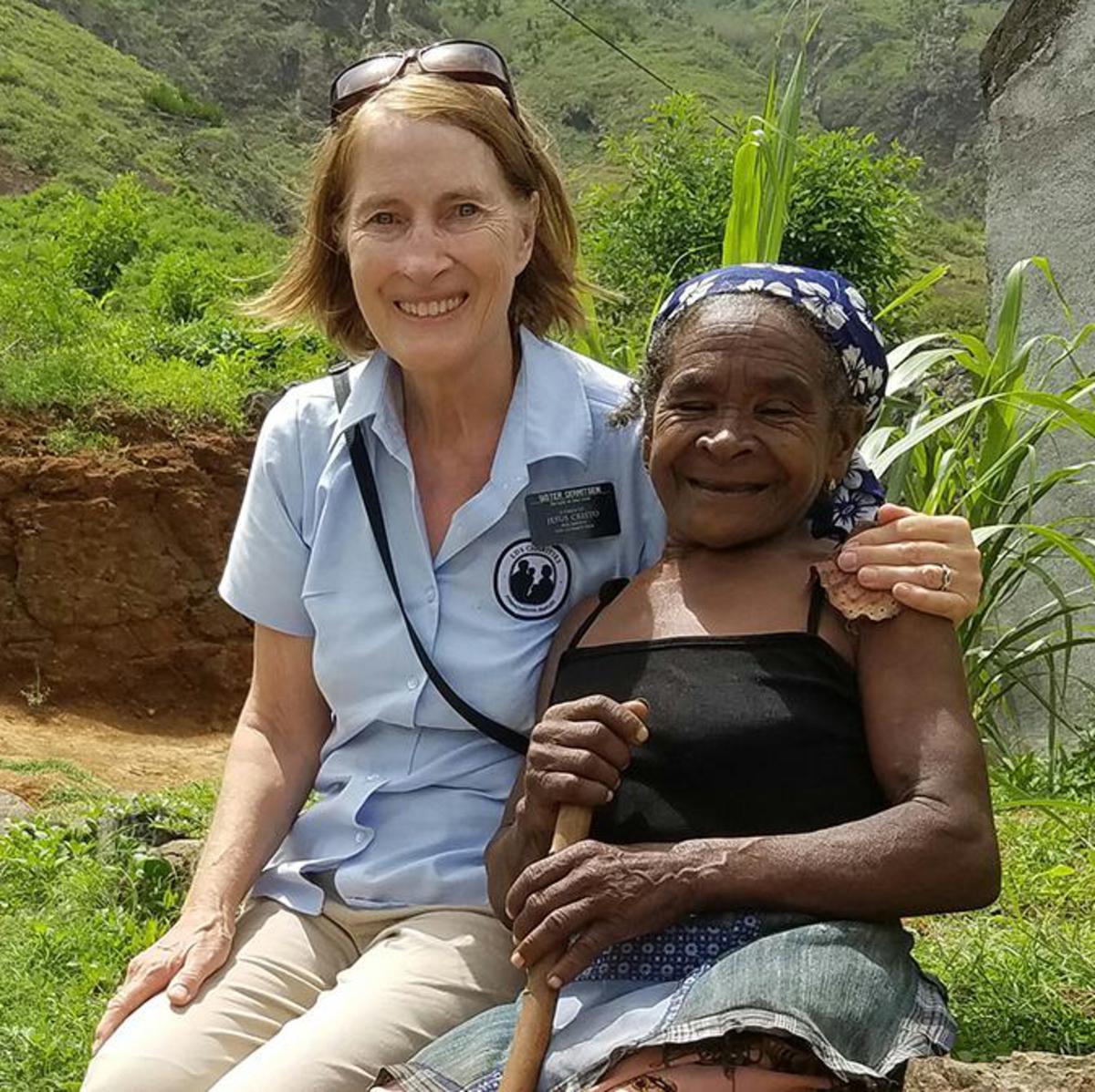 Zuster Gerritsen (links) naast Julia, een 71-jarige vrouw met cataract, een slechte heup en een schouderkwetsuur die dagelijks blootsvoets de steile helling naar haar huis beklimt.