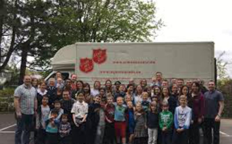a group of people in front of a salvation army truck