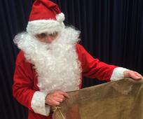 Der Weihnachtsmann hält den Sack auf, um die Geschenke von den Kindern zu empfangen.