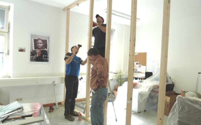 Drei Männer bauen eine Trennwand