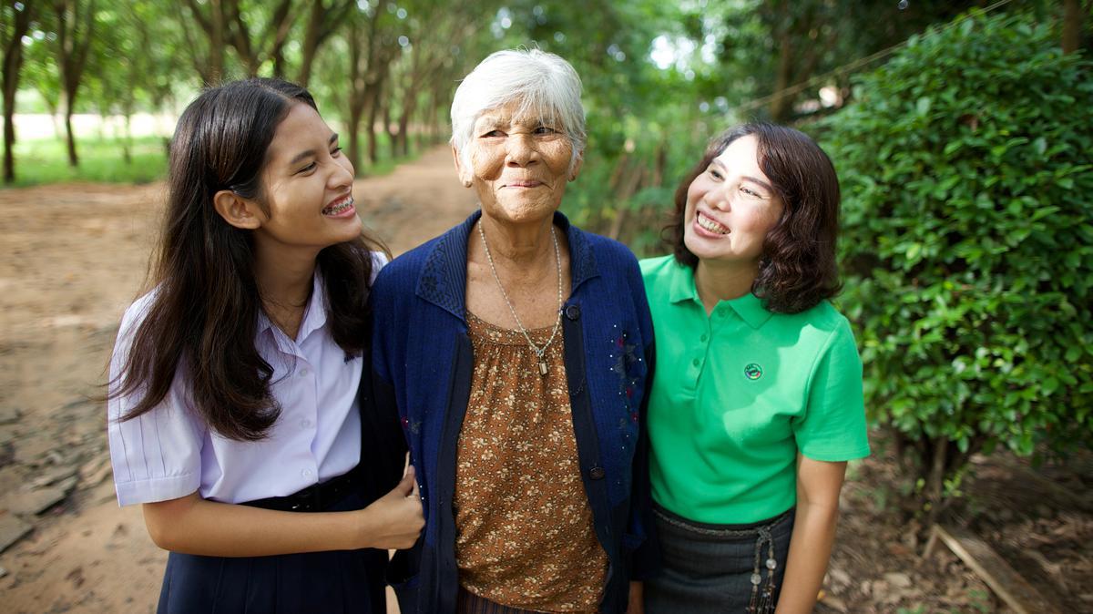 Een oudere vrouw wandelt met haar dochter en kleindochter op een paadje in Thailand.