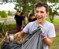 Un joven limpia de ramas un parque