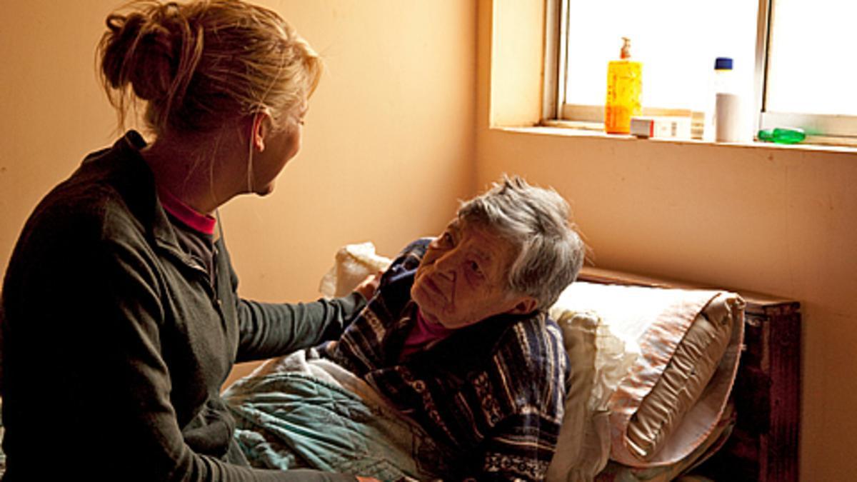 Una mujer cuida de una anciana enferma.