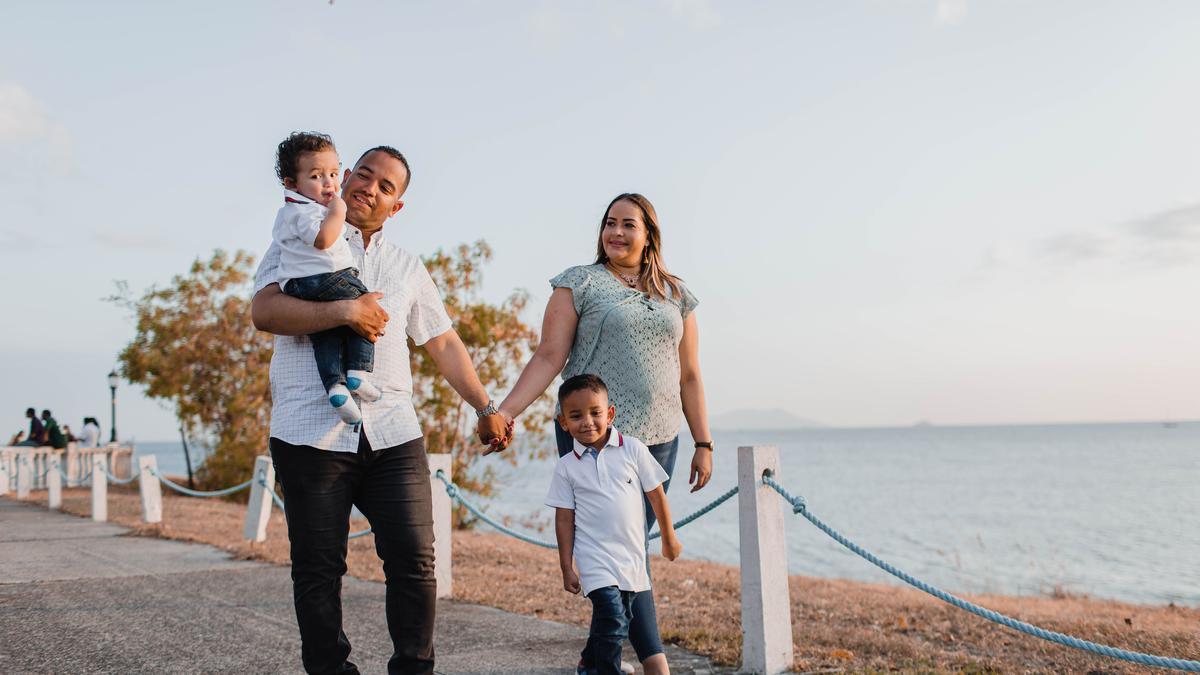 Padre, made e hijos caminando al lado de la playa.