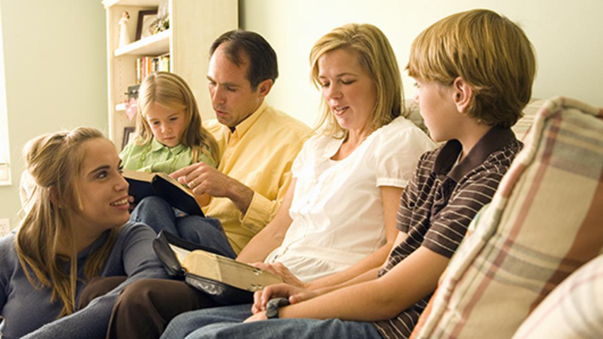 Padre, madre e hijos reunidos en la sala