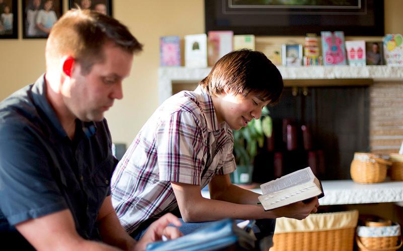 Padre e hijo leyendo las Escrituras