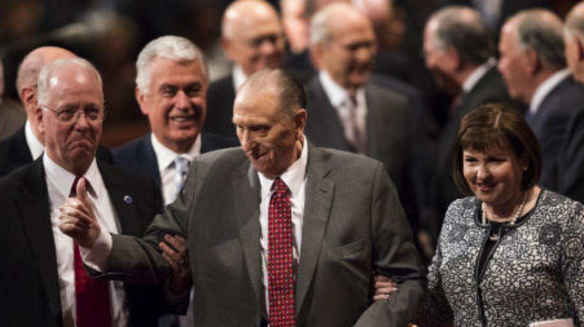 El presidente Thomas S. Monson, del brazo de su hija, sale de la sesión del sábado por la mañana de la Conferencia General del abril de 2017.