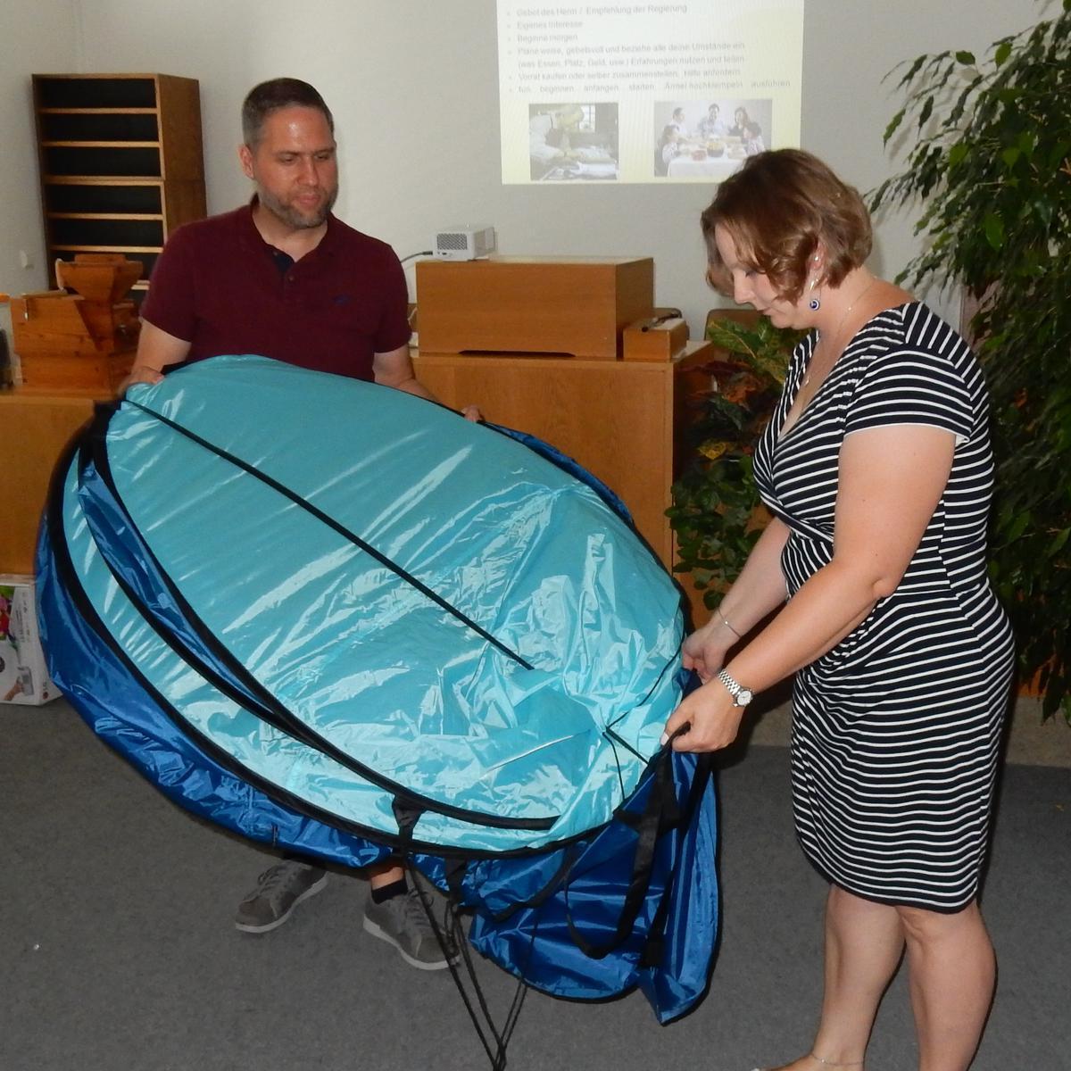 Schwester Sandra Bassler und Bruder Oliver Bassler demonstrieren, wie ein Pop-up-Zelt nach Gebrauch fachmännisch zusammengelegt wird.