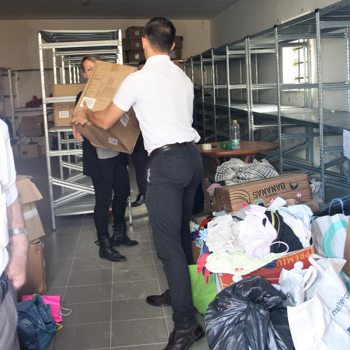 LDS missionaries and church members help organize and store donations in a camp warehouse.