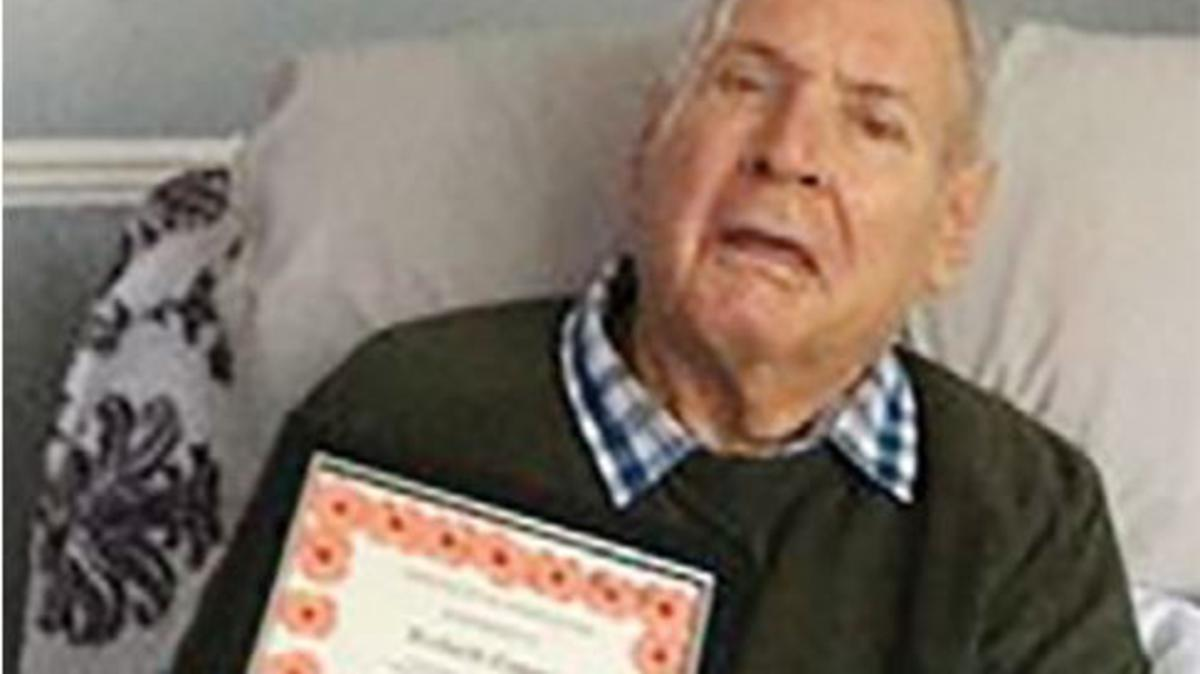 Richard Cooper holding the Royal British Legion award certificate