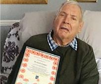 Richard Cooper holding the Royal British Legion award certificate.