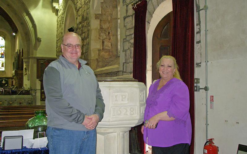 Rob and Judy Davies standing in front of the CofE font where Thomas Davies was christened in Upton Magna in 1812.