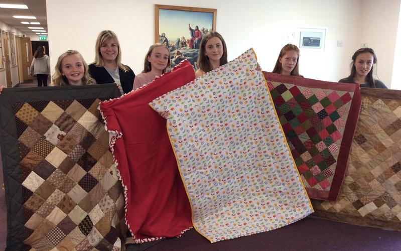 Women showing samples of blankets made
