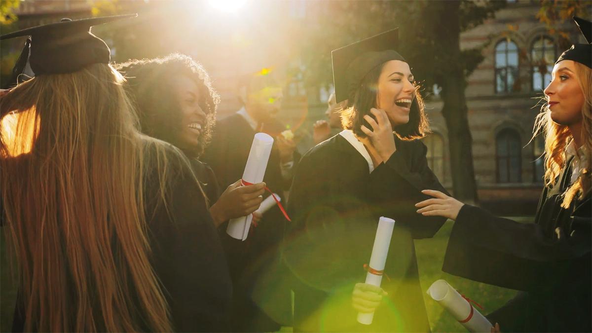 Μία ομάδα μαθητών χαμογελά, έχοντας μόλις αποφοιτήσει».