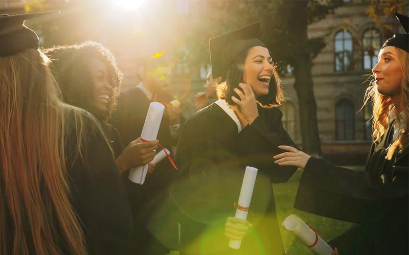 Um grupo de estudantes a sorrir, acabados de se formar