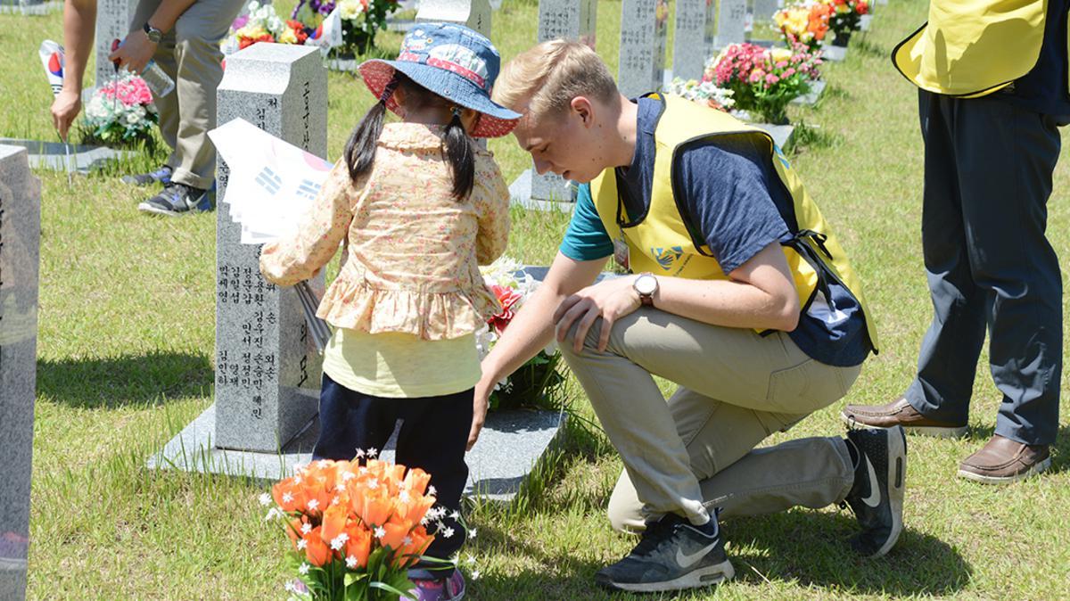 묘비를 닦고 있는 선교사와 어린아이