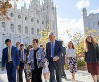 El presidente Dieter F. Uchtdorf y su esposa caminando junto con jóvenes adultos en la manzana del templo.