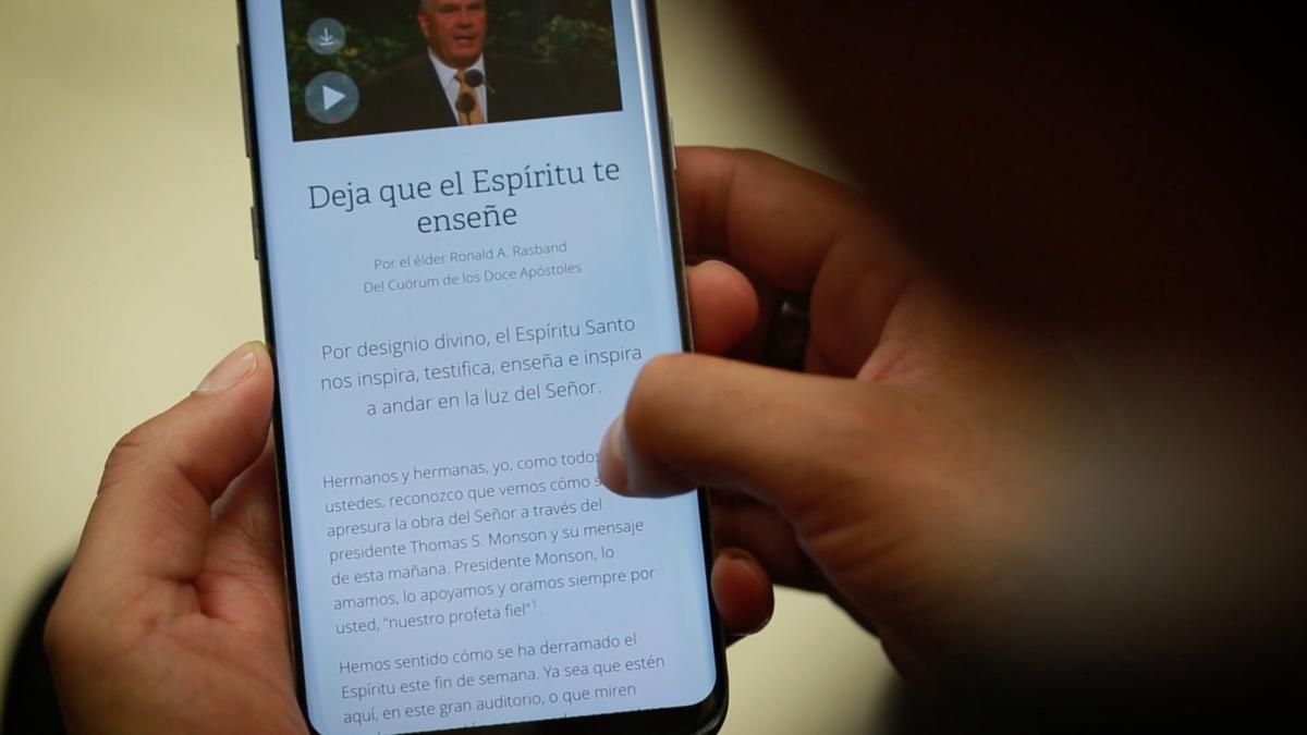 Persona leyendo mensaje de la conferencia general en su celular