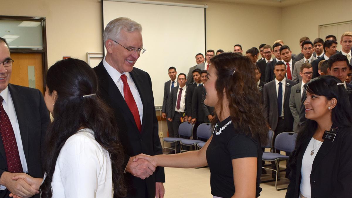 Élder Christofferson saludando a jóvenes durante el devocional