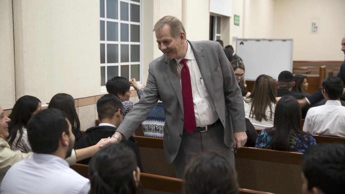 Élder Stevenson saludando a miembros durante una reunión.