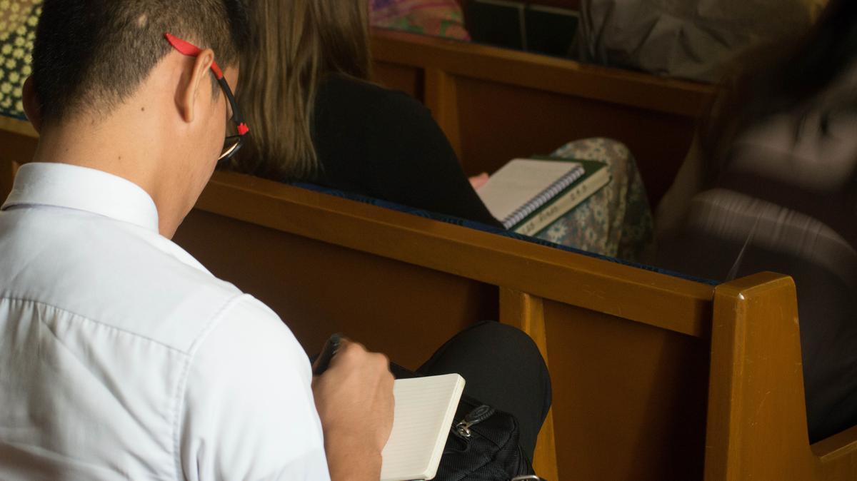 joven tomando notas durante una conferencia