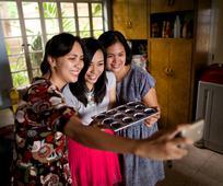 Hermanas tomándose una foto al cocinar.