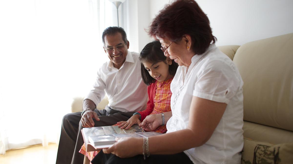 Abuelos y nieta mirando álbum de fotos