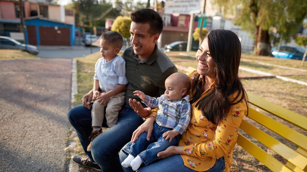 Familia sentada en una banca en el parque