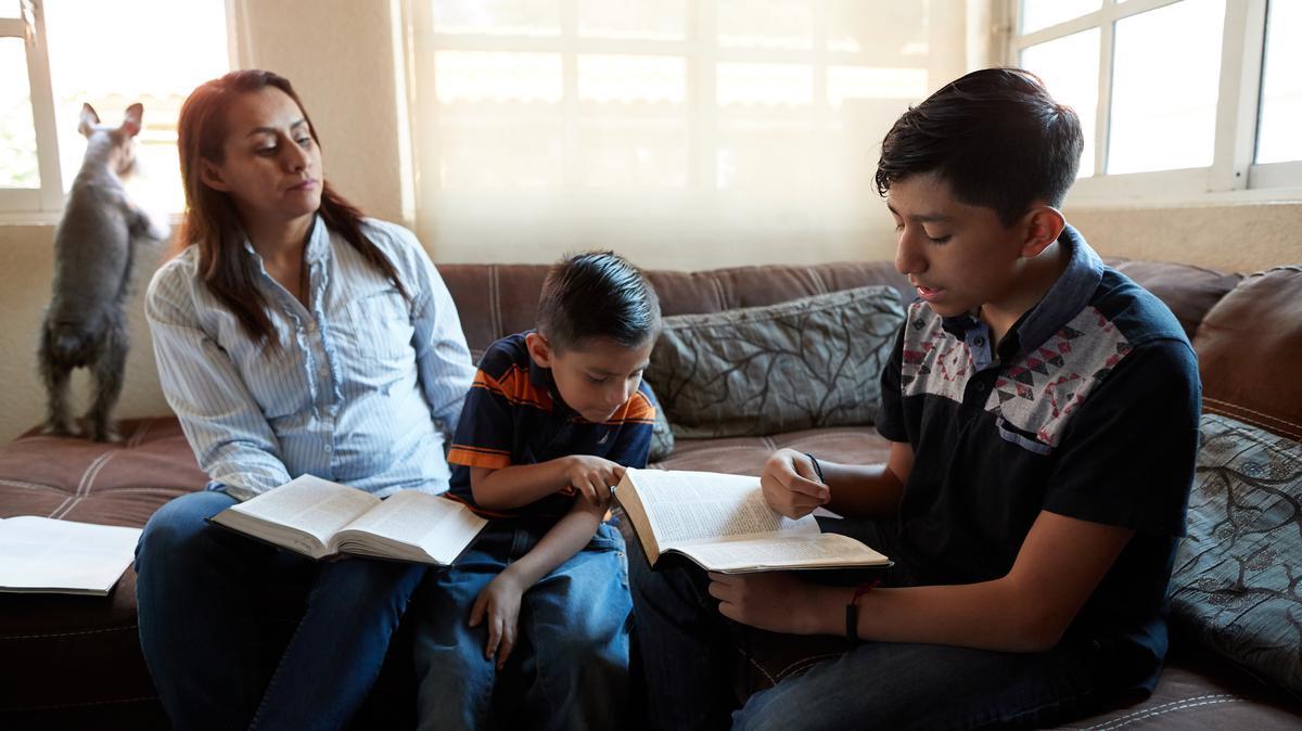 Madre e hijos estudiando las escrituras