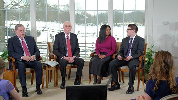 El presidente Eyring, el élder Holland y dos presentadores