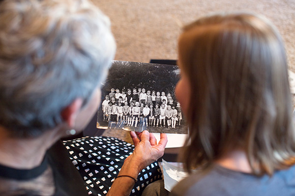 Women holding up an old family photo