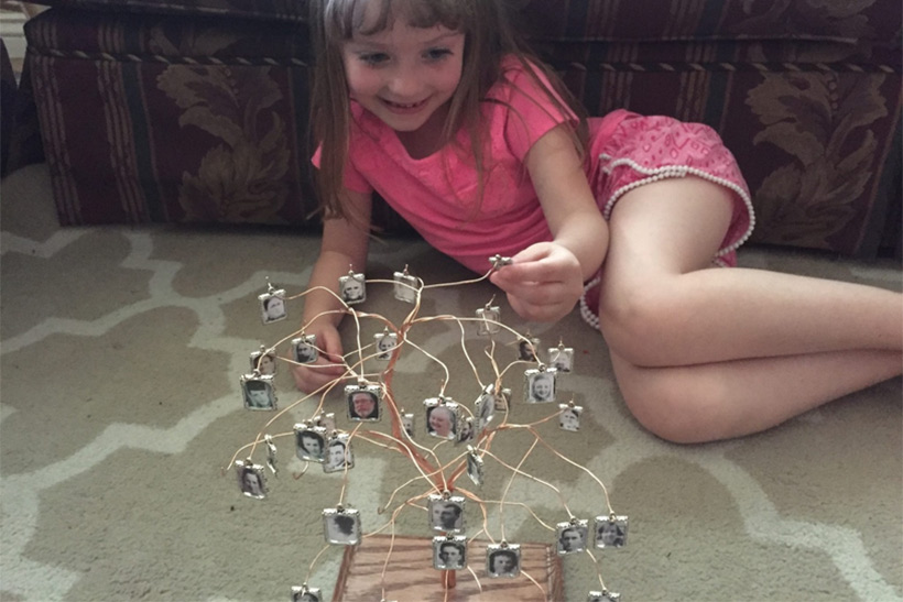 Image alt text: My daughter with a 3-D family tree. She gazes at it often, remembering who she is.