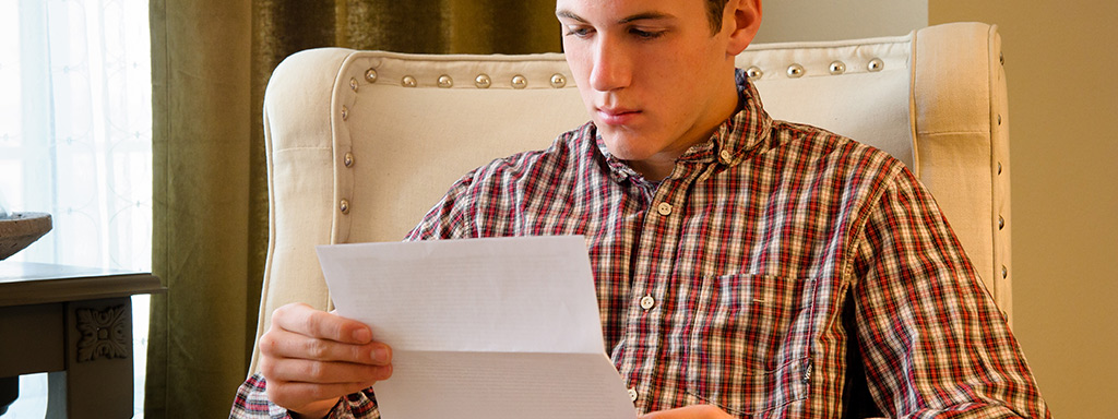 Young man reading a paper
