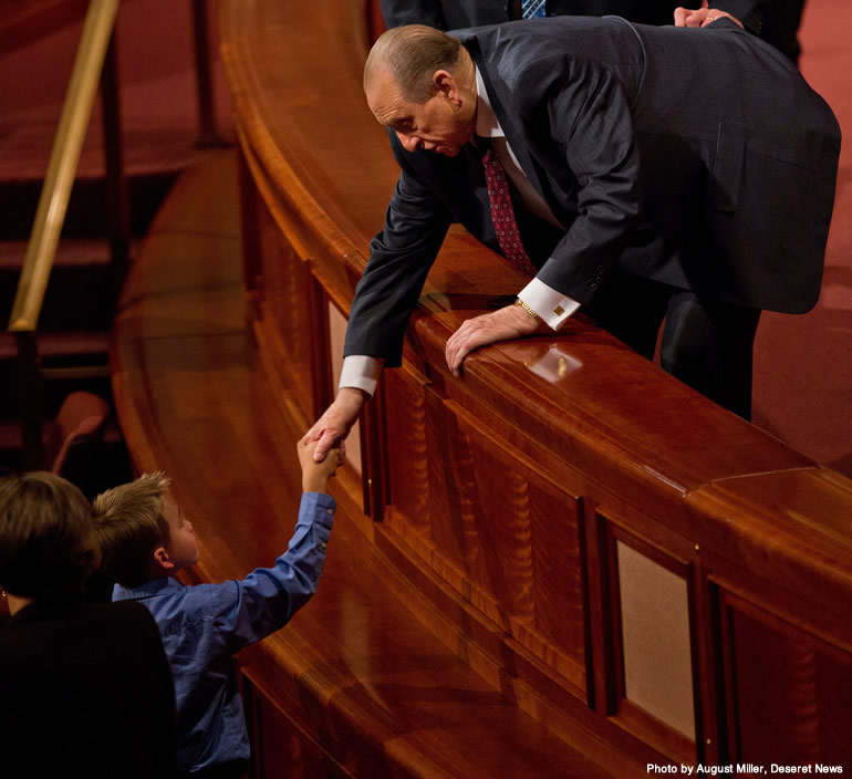 President Monson shaking a young boy's hand at conference