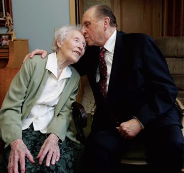 President Monson kissing the top of an elderly woman's head
