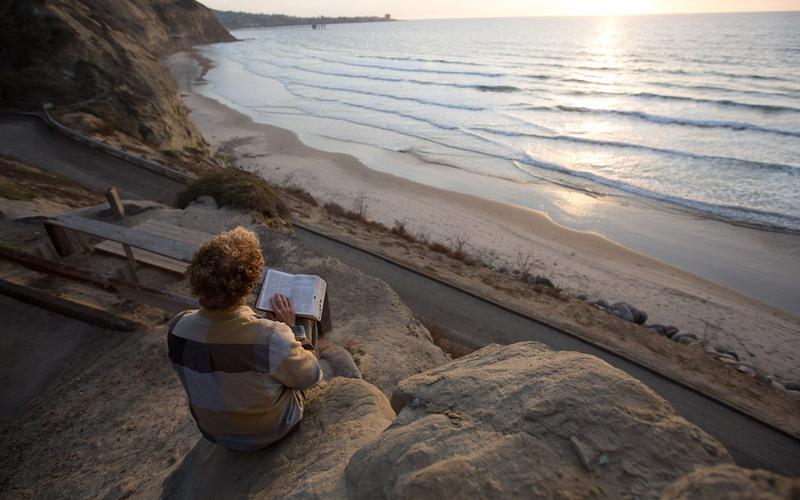 Boy reading scriptures by seashore