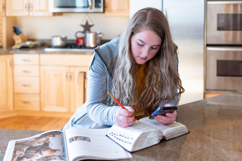 Girl studying in kitchen with scriptures, manual, and a smartphone