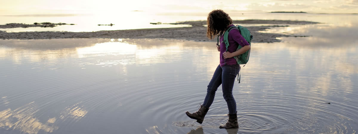 young woman walking through shallow water